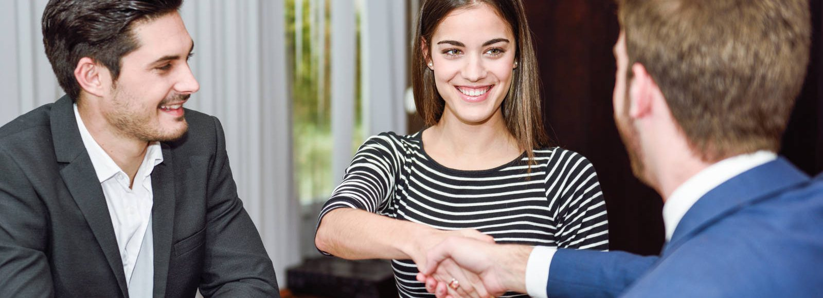 Smiling young couple shaking hands with an insurance agent or investment adviser